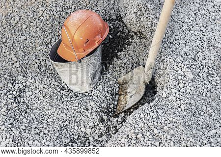 A Shovel Smeared In Concrete In A Heap Of Rubble For Preparing Concrete And An Orange Construction H