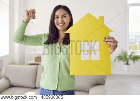 Happy Single Young Woman Smiling And Holding Paper House And Keys To Her New Home