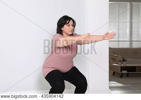 Overweight Mature Woman Squatting Near Wall At Home
