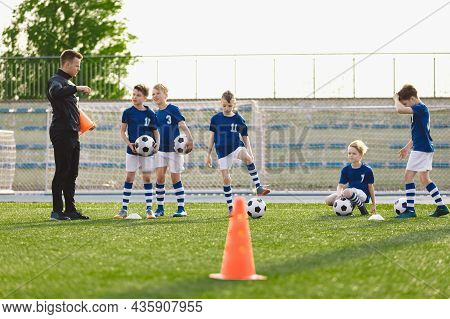 Group Of Boys On Soccer Training Field. Young Coach Explaining Drills Rules To Kids On Football Prac
