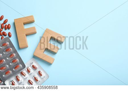 Wooden Letters Fe, Pills And Space For Text On Light Blue Background, Flat Lay. Anemia Concept