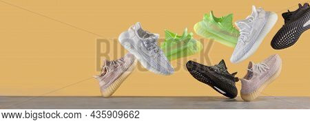 Flying Sneakers Isolated On A Yellow Background, Different Kind. Fashionable Stylish Sports Casual S