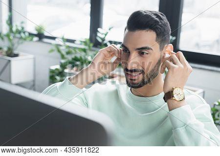 Smiling Arabian Businessman Holding Wireless Earphone Near Blurred Computer Monitor In Office