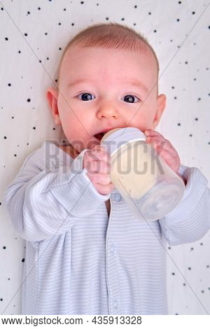 Happy Baby Is Smiling On Her Own Holding A Bottle Of Milk In Her Hands. Three Month Old Child Keeps