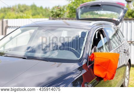 An Orange Warning Vest Is Hanging On The Mirror Of A Passenger Car. Car Breakdown Concept, Roadside