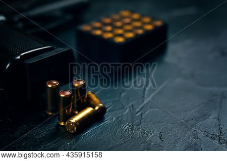 Black Gun With Cartridges On Table. Automatic Firearms With Bullets. Weapons On Concrete Background.