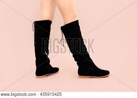 Woman's Legs In Black Long Winter Suede Boots Without Heels, With Flat Sole On Pink Background. Stud