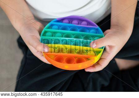 Faceless Little Boy Playing Pop It Rainbow Colors.