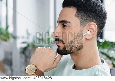 Side View Of Muslim Businessman In Wireless Earphone In Office