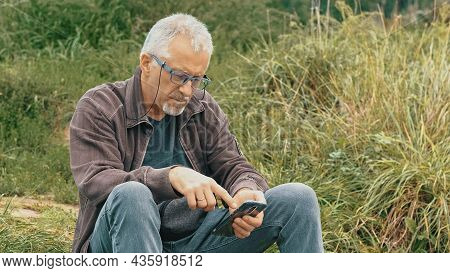 An Elderly Gray-haired, Bearded Man With Glasses Sits In Nature And Looks At The Phone On A Summer E