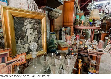 Palermo, Italy: Portrait Of Composer Mozart Inside A Second Hand Market With Old Furniture, Antique