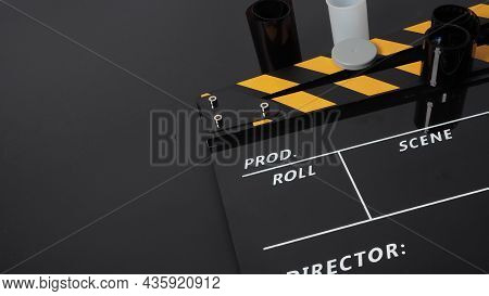 35mm Color Print Film And Clapper Board Or Movie Slate On Black Background. It Use In Movie And Vide