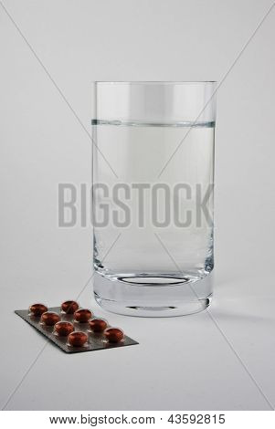 A glass of water and pills .