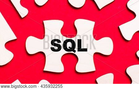 On A Bright Red Background, White Puzzles. In One Of The Pieces Of The Puzzle, The Text Sql Structur