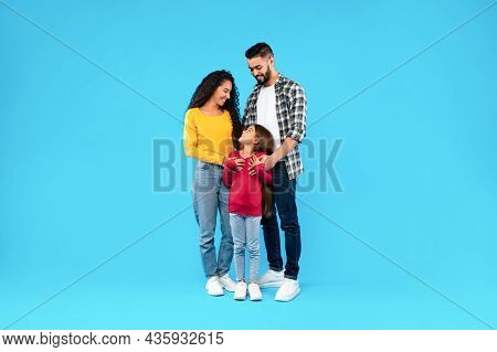 Middle-eastern Parents Embracing Their Happy Daughter On Blue Background