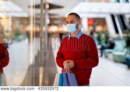 Shopping During Covid Pandemic Concept. Young Caucasian Guy In Face Mask Holding Shopper Bags At Sup
