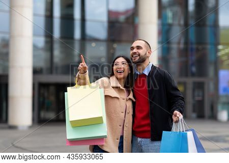 Multiracial Couple Walking Down Street With Shopper Bags, Pointing At New Store Or Ad, Going Shoppin