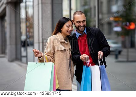 Affectionate Multinational Couple Standing Near Supermarket, Looking Inside Shopper Bags, Going Shop
