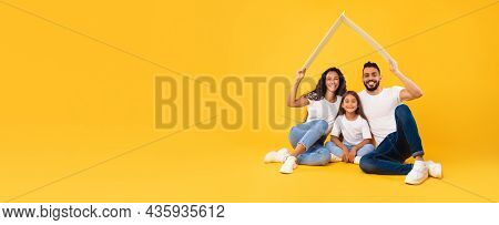 Family Middle-eastern Holding Symbolic House Roof Over Yellow Background, Panorama