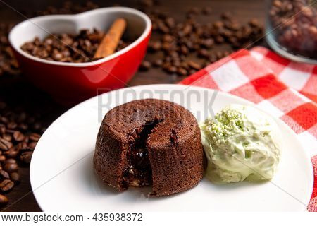 A Portion Of Chocolate Fondant With A Scoop Of Pistachio Ice Cream On A Plate. In The Background Is