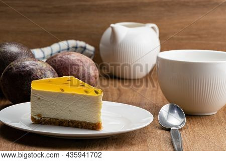 View Of Delicious Homemade Passion Fruit Cheesecake In White Ceramic Dish, A Cup Of Coffee, Ripe Pas