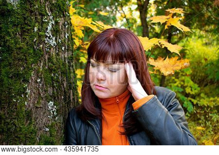 Red-haired Middle-aged Woman Is Having A Headache Or Migraine And Is Leaning On A Tree In The Park.