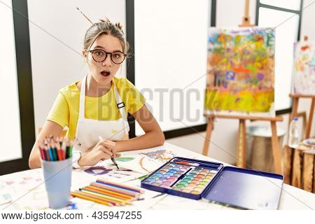 Young brunette teenager at art studio in shock face, looking skeptical and sarcastic, surprised with open mouth