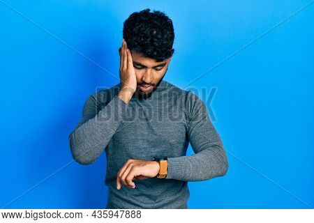 Arab man with beard wearing turtleneck sweater looking at the watch time worried, afraid of getting late
