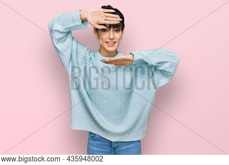 Young hispanic woman wearing casual clothes smiling cheerful playing peek a boo with hands showing face. surprised and exited