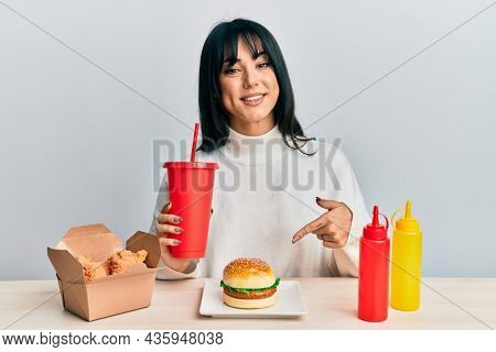 Young brunette woman with bangs eating a tasty classic burger with ketchup and mustard smiling happy pointing with hand and finger