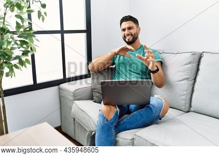 Young handsome man with beard using computer laptop sitting on the sofa at home disgusted expression, displeased and fearful doing disgust face because aversion reaction. with hands raised