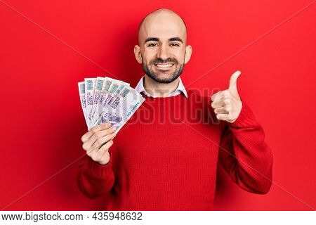 Young bald man holding egyptian pounds banknotes smiling happy and positive, thumb up doing excellent and approval sign