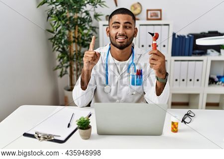 Young indian doctor holding ear otoscope smiling with an idea or question pointing finger with happy face, number one