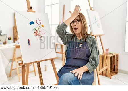 Middle age artist woman at art studio surprised with hand on head for mistake, remember error. forgot, bad memory concept.