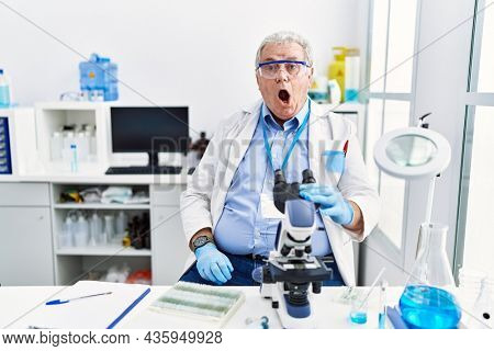 Senior caucasian man working at scientist laboratory in shock face, looking skeptical and sarcastic, surprised with open mouth