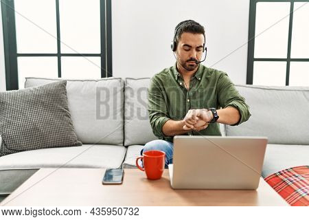 Young hispanic man with beard wearing call center agent headset working from home checking the time on wrist watch, relaxed and confident