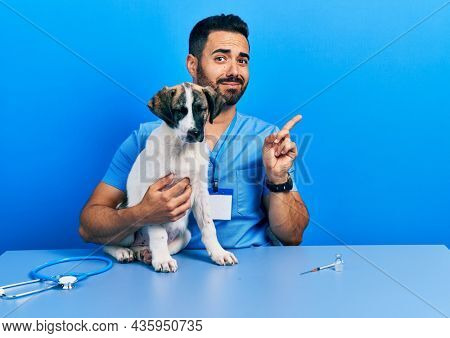 Handsome hispanic veterinary man with beard checking dog health pointing aside worried and nervous with forefinger, concerned and surprised expression