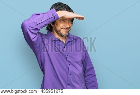 Middle age handsome man wearing business shirt very happy and smiling looking far away with hand over head. searching concept.