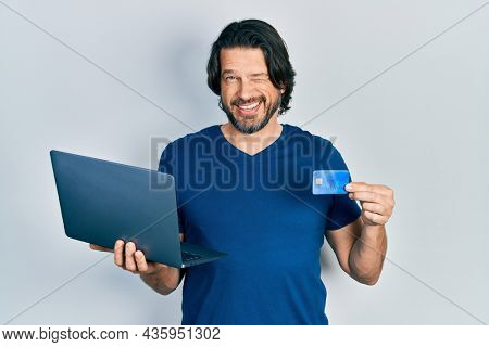 Middle age caucasian man wearing business style holding laptop and credit card winking looking at the camera with sexy expression, cheerful and happy face.