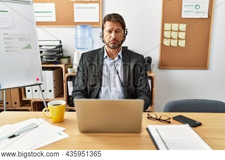 Handsome middle age man wearing call center agent headset at the office depressed and worry for distress, crying angry and afraid. sad expression.