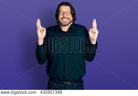 Middle age caucasian man wearing casual clothes and glasses gesturing finger crossed smiling with hope and eyes closed. luck and superstitious concept.
