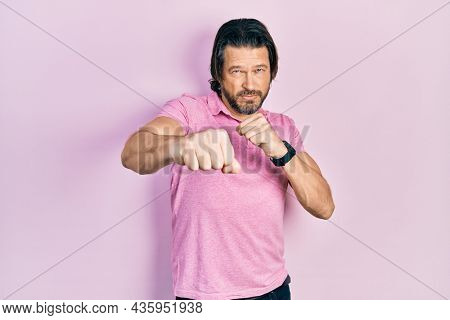 Middle age caucasian man wearing casual white t shirt punching fist to fight, aggressive and angry attack, threat and violence