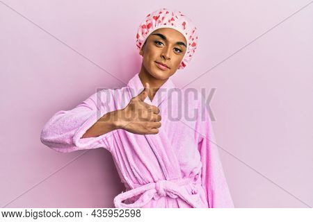 Hispanic man wearing make up wearing shower towel cap and bathrobe doing happy thumbs up gesture with hand. approving expression looking at the camera showing success.