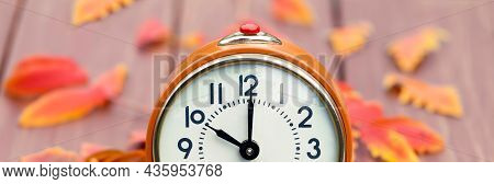 Orange Clock And Fall Autumn Leaves. Daylight Saving Time Banner.