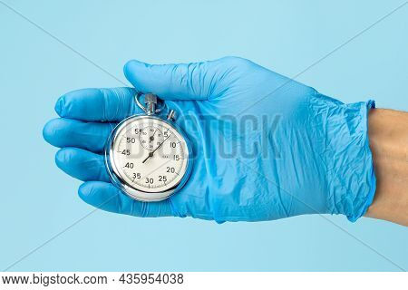 Stopwatch In The Hand Of A Doctor In A Glove On A Blue Background. Fast Medical Aid Concept