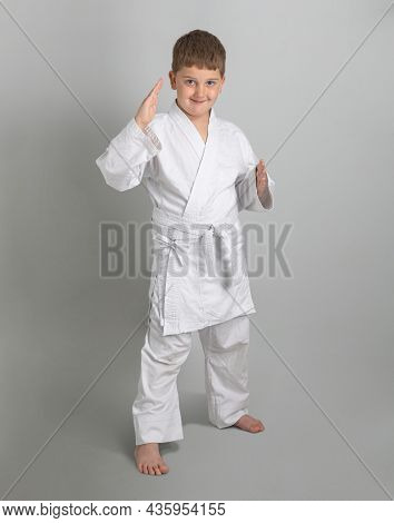 Boy In White Kimono Smiles And Stands In Combat Defensive Stance Against Gray Background