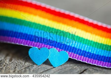 Two Blue Hearts As A Symbol Of Gay Love. Rainbow Ribbon Background In The Colors Of The Lgbt Communi