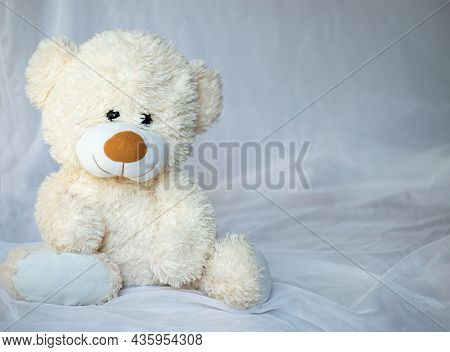 Teddy Smile Bear Is Sitting In Bed