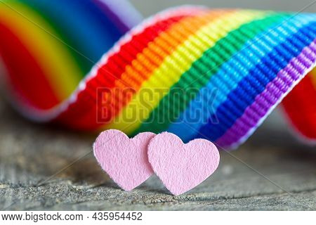 Two Pink Hearts As A Symbol Of Lesbian Love. Rainbow Ribbon Background In The Colors Of The Lgbt Com