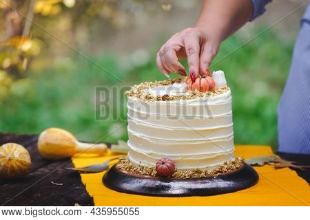 Woman Decorating A Pumpkin Pie Layer Cake  At A Garden Party. Unrecognizable Woman Decorating Cake W